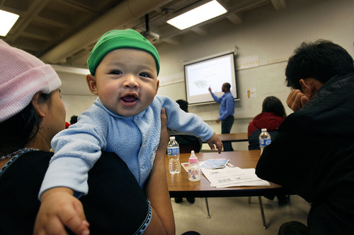Scott Sommerdorf  |  The Salt Lake Tribune              Five-month-old Same Sei is held by his mother Paw Lah as his father Ko Sei (right) listens to Carlos Linares at an anti-discrimination workshop Saturday for refugees of the Karen community to educate residents about employment law and resources. The office partnered with the Utah Labor Commission, Workers Compensation Fund and American Civil Liberties Union to gather the curriculum for the workshop.