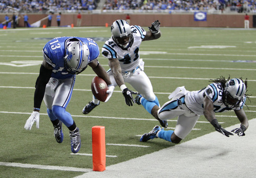 Detroit Lions wide receiver Nate Burleson scores a touchdown on a 16-yard reception as Carolina Panthers cornerback Captain Munnerlyn (41) and strong safety Charles Godfrey (30) defend in the third quarter of an NFL football game in Detroit, Sunday, Nov. 20, 2011. (AP Photo/Paul Sancya)