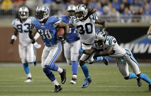 Detroit Lions running back Kevin Smith (30) breaks away from Carolina Panthers strong safety Charles Godfrey (30) and free safety Sherrod Martin (23) during the second quarter of an NFL football game in Detroit, Sunday, Nov. 20, 2011. (AP Photo/Duane Burleson)