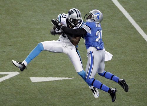 Carolina Panthers wide receiver Brandon LaFell (11) catches a pass as Detroit Lions cornerback Eric Wright (21) defends in the first quarter of an NFL football game in Detroit, Sunday, Nov. 20, 2011. (AP Photo/Paul Sancya)