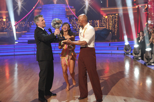 In this image released by ABC-TV, war veteran and actor J.R. Martinez, right, and his partner Karina Smirnoff hold their award with host Tom Bergeron after they were crowned champions of the celebrity dance competition series,