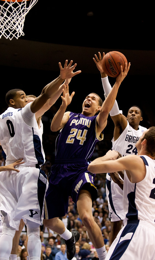 Prairie View A&M's Ryan Gesiakowski drives to the basket as BYU's Brandon Davies (0) and Damarcus Harrison (24) during an NCAA college basketball game at the Marriott Center in Provo, Utah, on Tuesday, Nov. 22, 2011. (AP Photo/The Daily Herald, Spenser Heaps)