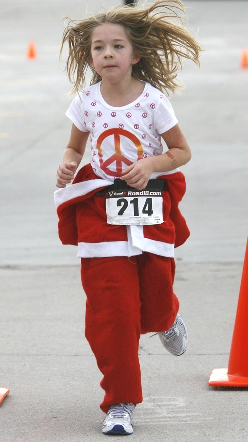 Rick Egan  | The Salt Lake Tribune  Eight-year-old Michelle Filipouvic (214) crosses the finish line at the Santa Run 5K, minus the hat, the beard and coat she started with, at Valley Fair Mall on Friday.