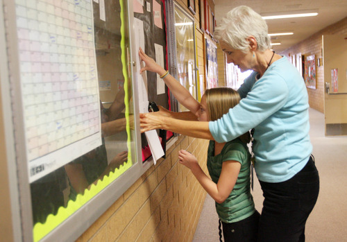 Kim Raff | The Salt Lake Tribune Gloria Kidd and her granddaughter, Maddy Leavitt, hang up fliers in the lobby of Hillside Elementary School in West Valley City. A new BYU study shows that kids who have good relationships with grandparents are more engaged in school and have better social behaviors. Kidd works in the office at the school and gets to see two of her grandkids who are students there.