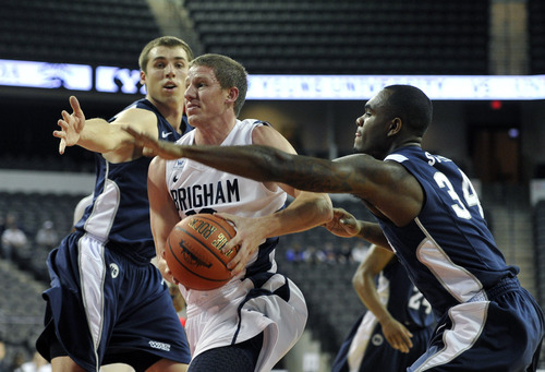 Nevada's Olek Czyz, left, and Malik Story (34) defend as Brigham Young's Brock Zylstra, center, drives to the basket during the first half of an NCAA college basketball game on Friday, Nov. 25, 2011, in Hoffman Estates, Ill. (AP Photo/Jim Prisching)