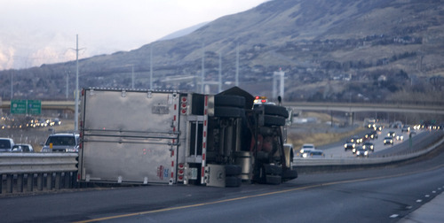 Al Hartmann  |  The Salt Lake Tribune  Asemitruck lies on its side along the shoulder of I-15 northbound near Farmington on Thursday morning. I-15 was closed Thursday morning to high-profile vehicles due to the high winds in Davis County. A wind gust was recorded at 100 mph in Centerville.