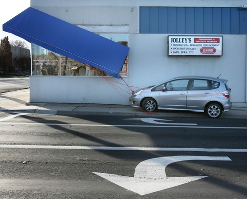 Steve Griffin  |  The Salt Lake Tribune An awning at Jolley's Corner Pharmacy in Salt Lake City is tied to a car on Thursday to prevent it from blowing away.