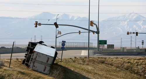 Leah Hogsten | The Salt Lake Tribune   A semitruck toppled in the wind on Park Lane in Farmington. Hurricane-force winds, in places topping 100 mph, ripped through Utah on Thursday, overturning semitrailer rigs on Interstate 15, toppling trees and triggering widespread power outages affecting nearly 50,000 homes and businesses.