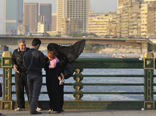 An Egyptian family is seen on a bridge over the Nile River near Tahrir Square in Cairo, Egypt, Saturday, Dec. 3, 2011. (AP Photo/Bela Szandelszky)