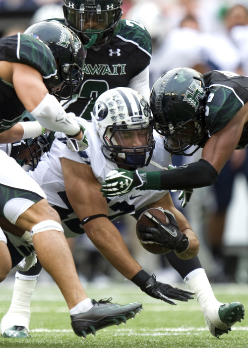 BYU running back Michael Alisa (42) is tackled by Hawaii defenders in the second quarter of an NCAA college football game on Saturday, Dec. 3, 2011, in Honolulu. (AP Photo/Eugene Tanner)