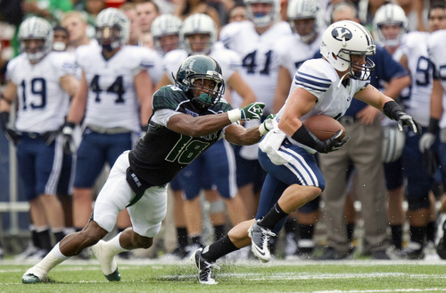 BYU wide receiver JD Falslev, right, escapes the grasp of Hawaii cornerback Mike Sellers (18) in the second quarter of an NCAA college football game on Saturday, Dec. 3, 2011, in Honolulu. (AP Photo/Eugene Tanner)
