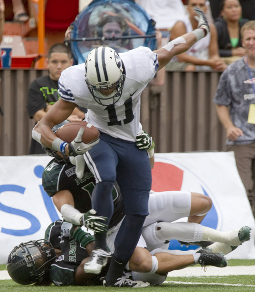 BYU wide receiver Ross Apo (11) manages to escape from Hawaii cornerback Tank Hopkins, bottom, and safety Richard Torres (19) to score a touchdown in the third quarter of an NCAA college football game, Saturday, Dec. 3, 2011, in Honolulu. (AP Photo/Eugene Tanner)