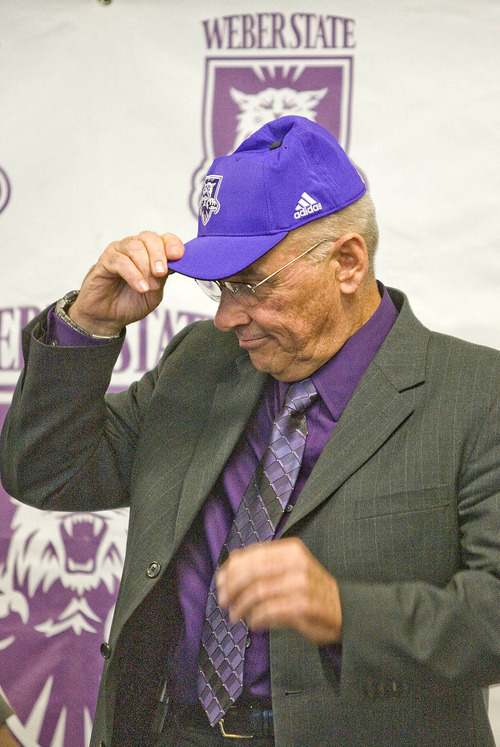 Paul Fraughton | The Salt Lake Tribune John L. Smith dons a purple Weber State cap at  the press conference where he was introduced   as Weber State's new head football coach.   Tuesday, December 6, 2011