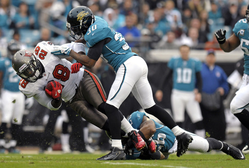 Tampa Bay Buccaneers running back Kregg Lumpkin (28) is brought down by Jacksonville Jaguars defensive back Drew Coleman (30) and free safety Dawan Landry during the first half of an NFL football game on Sunday, Dec. 11, 2011, in Jacksonville, Fla. (AP Photo/Phelan M. Ebenhack)