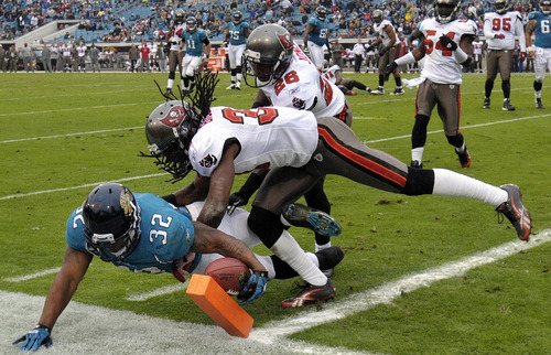 Jacksonville Jaguars running back Maurice Jones-Drew (32) dives for a touchdown under the tackle of Tampa Bay Buccaneers defensive back E.J. Biggers (31) during the first half of an NFL football game on Sunday, Dec. 11, 2011, in Jacksonville, Fla. (AP Photo/Stephen Morton)