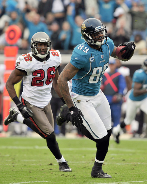 Jacksonville Jaguars tight end Marcedes Lewis (89) runs for yardage against Tampa Bay Buccaneers strong safety Sean Jones (26) during the first half of an NFL football game on Sunday, Dec. 11, 2011, in Jacksonville, Fla. (AP Photo/Stephen Morton)