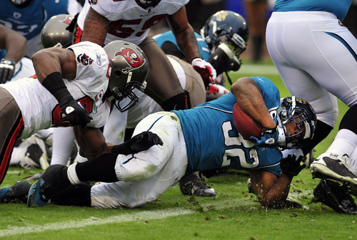 Jacksonville Jaguars running back Maurice Jones-Drew (32) scores a touchdown during the first half of an NFL football game against the Tampa Bay Buccaneers on Sunday, Dec. 11, 2011, in Jacksonville, Fla. (AP Photo/Stephen Morton)