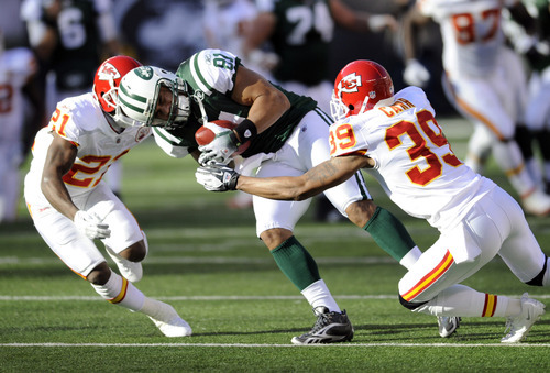 New York Jets' Dustin Keller, center, is tackled by Kansas City Chiefs' Javier Arenas, left, and Brandon Carr during the first quarter of the NFL football game on Sunday, Dec. 11, 2011, in East Rutherford, N.J. (AP Photo/Bill Kostroun)
