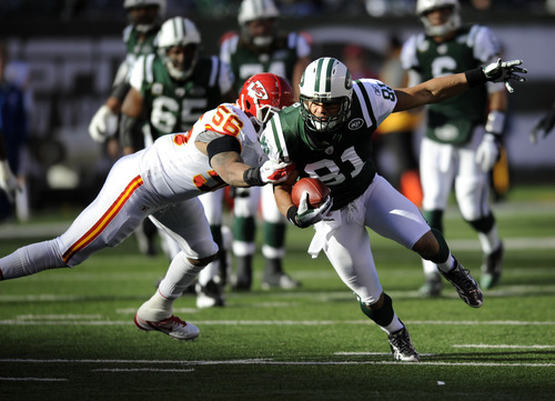New York Jets' Dustin Keller, right, is tackled by Kansas City Chiefs' Derrick Johnson during the first quarter of the NFL football game Sunday, Dec. 11, 2011, in East Rutherford, N.J. (AP Photo/Bill Kostroun)