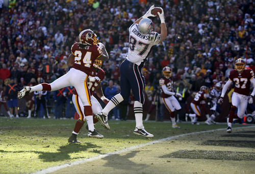 New England Patriots tight end Rob Gronkowski (87) catches a touchdown pass over Washington Redskins strong safety DeJon Gomes (24) during the first half of an NFL football game on Sunday, Dec. 11, 2011, in Landover, Md.  (AP Photo/Evan Vucci)