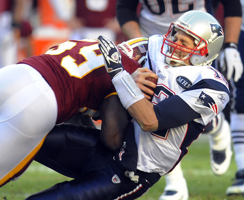New England Patriots quarterback Tom Brady (12) is hit by Washington Redskins inside linebacker London Fletcher (59) during the first half of an NFL football game on Sunday, Dec., 11, 2011, in Landover, Md. (AP Photo/Rich Lipski)