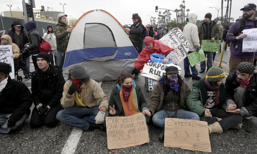Protestors sit in the middle of the street at the port of Long Beach in Long Beach, Calif. on Monday, Dec 12, 2011. Hundreds of protesters blocked gates at some of the West Coast's busiest ports on Monday, delaying truck traffic in a day of demonstrations that organizers hope will cut into the profits of the corporations that run the docks.   (AP Photo/Nick Ut)