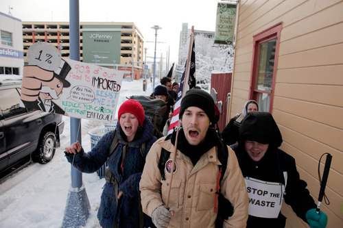 From left, Tina Robinson, Ben Fricke and Terrence van Ettinger march with the Occupy Anchorage protesters to the Integrated Concepts & Research Corporation (ICRC) office near the Port of Anchorage on Monday, Dec. 12, 2011. ICRC is a major contractor on the Port of Anchorage expansion, a project which Occupy Anchorage claims has been mismanaged and wasteful. The protesters joined other West Coast anti-Wall Street protesters in taking a stand against problems at ports. (AP Photo/Loren Holmes)