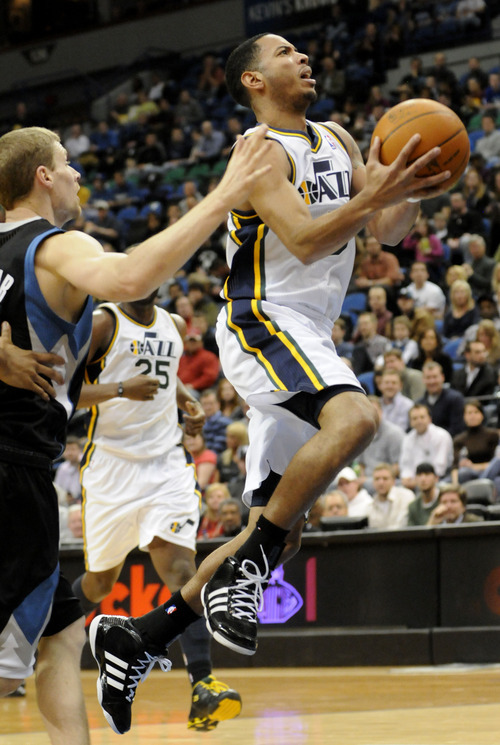 Utah Jazz's Devin Harris lays up as Minnesota Timberwolves' Luke Ridnour, left, defends in the first half of an NBA basketball game Friday, March 11, 2011 in Minneapolis. (AP Photo/Jim Mone)