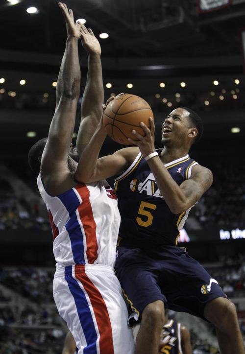 Utah Jazz guard Devin Harris (5) drives on Detroit Pistons forward Jason Maxiell (54) in the second half of an NBA basketball game in Auburn Hills, Mich., Saturday, Feb. 26, 2011. Detroit won 120-116. (AP Photo/Paul Sancya)