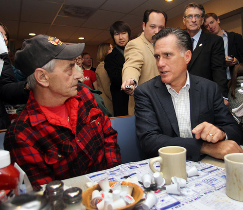 Republican presidential candidate, former Massachusetts Gov. Mitt Romney talks to Bob Garon during a campaign stop at the Chez Vachon Restaurant , Monday, Dec. 12, 2011 in Manchester, N.H. (AP Photo/Jim Cole)