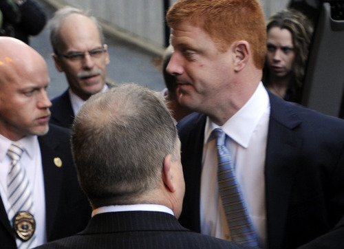 Penn State assistant football coach Mike McQueary, right, arrives at Dauphin County Court surrounded by heavy security Friday, Dec 16, 2011, in Harrisburg, Pa. McQueary declined to speak to reporters Friday as he entered the courthouse in Harrisburg for the hearing for Gary Schultz and Tim Curley, who are set to appear for a preliminary hearing related to the Jerry Sandusky child sex abuse case. (AP Photo/Bradley C Bower)