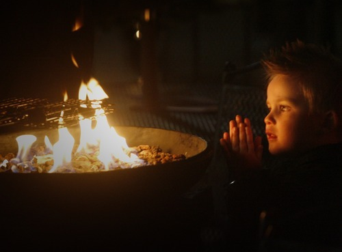 Rick Egan  | The Salt Lake Tribune  Three-year-old Bryton Roper, of Provo, warms his hands by the fire at the Christmas Village in Ogden at its opening this year. The village has been a tradition in Ogden since 1962.