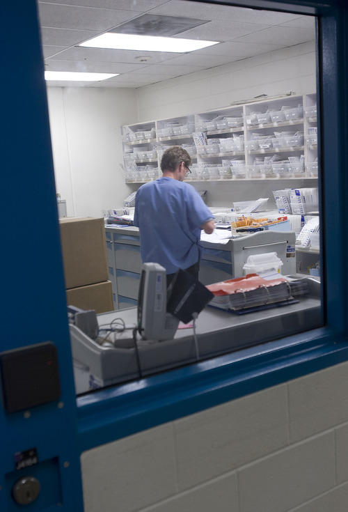 Al Hartmann  |  The Salt Lake Tribune At the medical unit in Salt Lake County's Adult Detention Center, a pharmacy worker fills prescriptions behind a secure steel door.