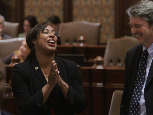 Illinois Sen. Toi Hutchinson, D-Chicago Heights, left, reacts as the tax break legislation passes while on the Senate floor during session Tuesday, Dec. 13, 2011 in Springfield. Illinois Rep. John E. Bradley, D-Marion, right, looks on. The Senate sent the $330 million tax-relief package to Illinois Gov. Pat Quinn Tuesday after House approval a day earlier. (AP Photo/Seth Perlman)