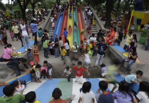 Filipino children play at Manila's Rizal Park, Philippines on Christmas day Sunday Dec. 25, 2011. Christmas is one of the most important holidays in this predominantly Roman Catholic nation. (AP Photo/Aaron Favila)