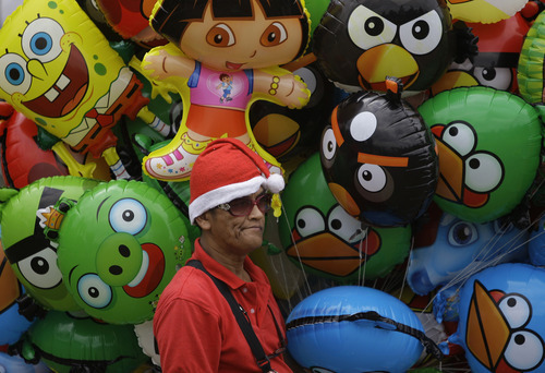 Filipino Irineo Ayon Sr. sells balloons at Manila's Rizal Park, Philippines on Christmas day Sunday Dec. 25, 2011. Christmas is one of the most important holidays in this predominantly Roman Catholic nation. (AP Photo/Aaron Favila)