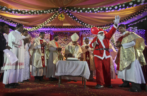 Indian Catholic priests celebrate Christmas by cutting a cake at St. Mary's church in Hyderabad, India, Sunday, Dec.25, 2011. (AP Photo/Mahesh Kumar A.)