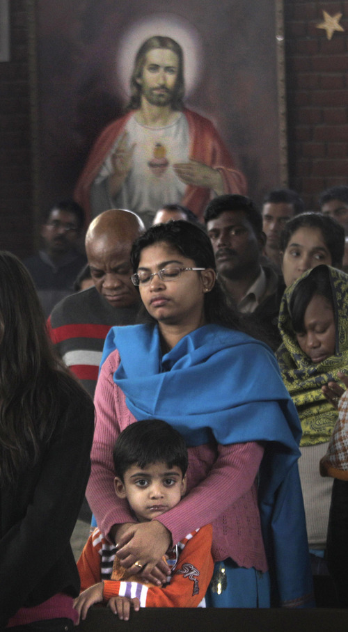 Devotees pray as a portrait of Jesus Christ hangs at a church on Christmas in New Delhi, India, Sunday, Dec. 25, 2011. Christmas Day is observed as a national holiday in India. (AP Photo/ Manish Swarup)