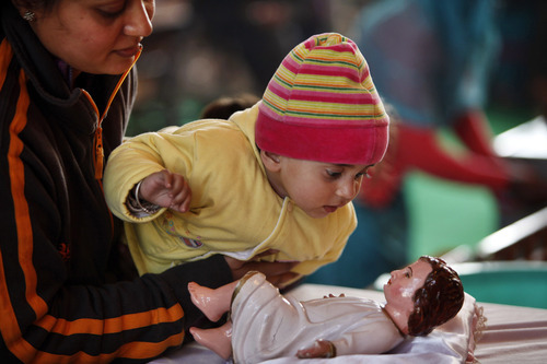 A child touches an idol of baby Jesus in a church, in Jammu, India, Sunday, Dec.25,2011. Christmas Day is observed as a national holiday in India. (AP Photo/Channi Anand)