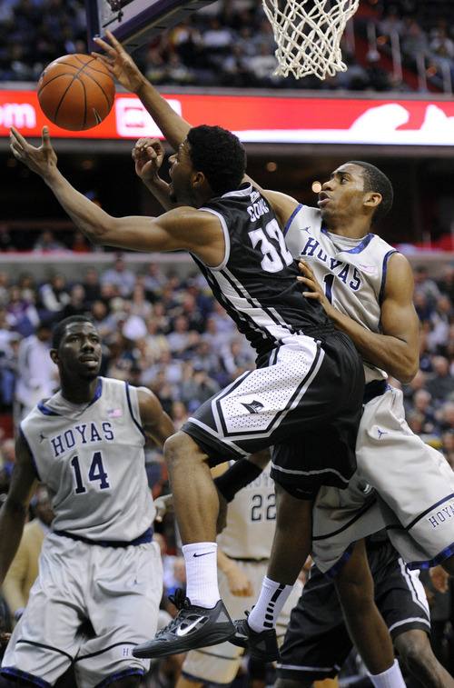 Georgetown forward Hollis Thompson, right, battles for the ball against Providence guard Vincent Council, left, during the first half of an NCAA college basketball game, Saturday, Dec. 31, 2011, in Washington. Georgetown center Henry Sims (14) looks on. (AP Photo/Nick Wass)