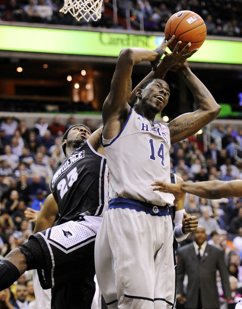 Providence forward LaDontae Henton (23) battles for the ball against Georgetown center Henry Sims (14) during the second half of an NCAA college basketball game, Saturday, Dec. 31, 2011, in Washington. Georgetown won 49-40. (AP Photo/Nick Wass)