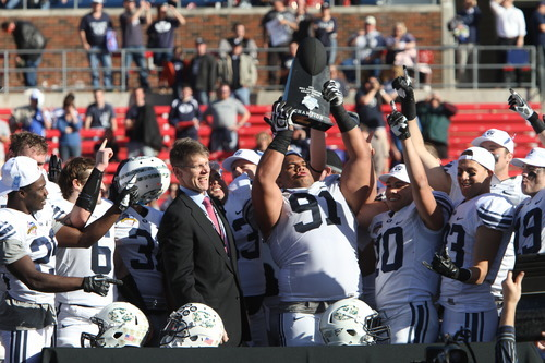 Rick Egan  | The Salt Lake Tribune   Brigham Young Cougars defensive lineman Hebron Fangupo (91) holds the trophy above his head, as Cougars Seniors are presented thein the Armed Forces Bowl Trophy, in Dallas, Texas, Friday, December 30, 2011
