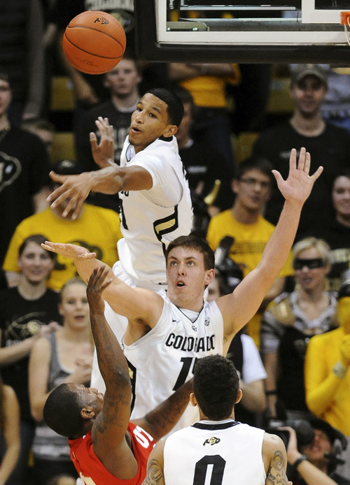 Colorado's Andre Roberson, top, blocks a shot by Utah's Josh Watkins as Colorado's Shane Harris-Tunks defends during the second half of an NCAA college basketball game, Saturday, Dec. 31, 2011, in Boulder, Colo. Colorado won 73-33. (AP Photo/The Daily Camera, Cliff Grassmick) NO SALES; NO MAGS; NO TV