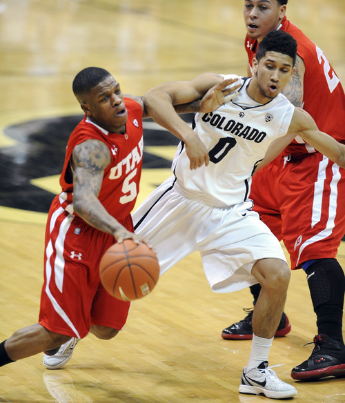 Utah's Kareem Storey (5) collides with Colorado's Askia Booker (0) during the first half of an NCAA college basketball game, Saturday, Dec. 31, 2011, in Boulder, Colo. (AP Photo/The Daily Camera, Cliff Grassmick) NO SALES; NO MAGS; NO TV