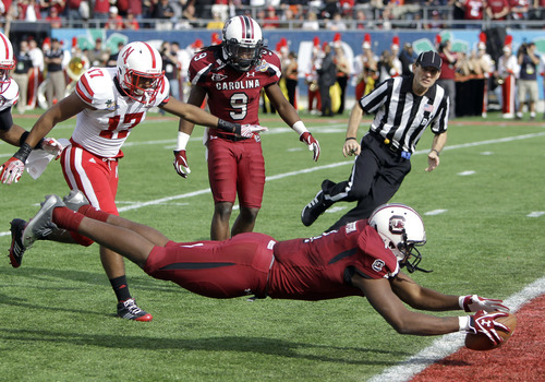 South Carolina wide receiver Alshon Jeffery, right, dives across the goal line past Nebraska cornerback Ciante Evans (17) for a 51-yard touchdown pass play as time runs out in the first half of the Capital One Bowl NCAA college football game, Monday, Jan. 2, 2012, in Orlando, Fla. (AP Photo/John Raoux)