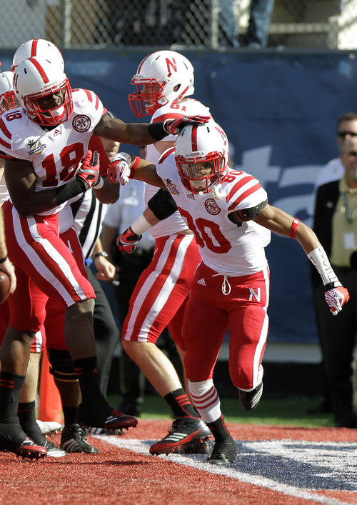 Nebraska wide receiver Kenny Bell (80) celebrates with teammates including wide receiver Quincy Enunwa (18) after catching a 30-yard pass for a touchdown against South Carolina during the first half of the Capital One Bowl NCAA college football game, Monday, Jan. 2, 2012, in Orlando, Fla. (AP Photo/John Raoux)