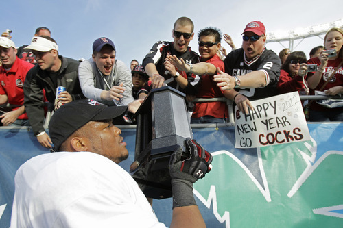 South Carolina guard Terrence Campbell, lower left, carries the championship trophy around the field for fans to enjoy after South Carolina defeated Nebraska 30-13 in the Capital One Bowl NCAA college football game, Monday, Jan. 2, 2012, in Orlando, Fla. (AP Photo/John Raoux)
