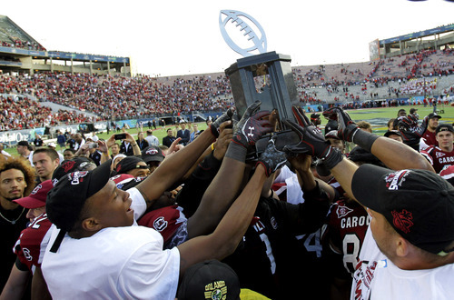 South Carolina players hold up the championship trophy after defeating Nebraska 30-13 in the Capital One Bowl NCAA college football game, Monday, Jan. 2, 2012, in Orlando, Fla. (AP Photo/John Raoux)