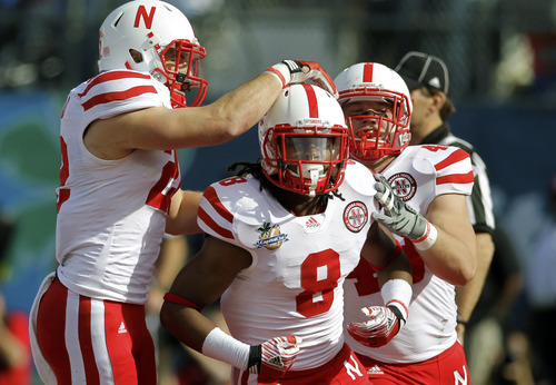 Nebraska running back Ameer Abdullah (8) celebrates his 1-yard touchdown run against South Carolina with teammates Rex Burkhead, left, and Tyler Legate during the first half of the Capital One Bowl NCAA college football game, Monday, Jan. 2, 2012, in Orlando, Fla. (AP Photo/John Raoux)