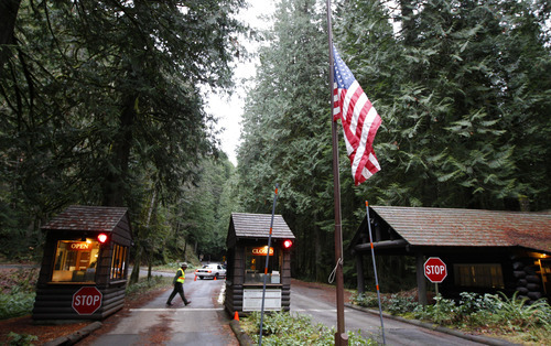 The flag at an entrance to Mount Rainier National Park in Washington state flies at half-staff, Monday, Jan. 2, 2012, the day after Park Ranger Margaret Anderson was killed by a gunman inside the park. The park remained closed Monday as officials search for the gunman, who remains at-large after he fled on foot. (AP Photo/Ted S. Warren)